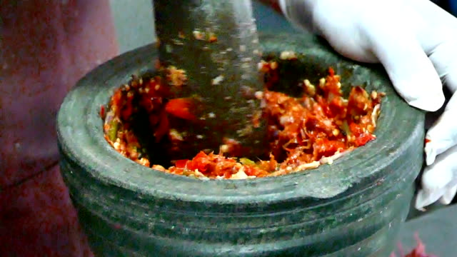 4K footage, close up hand pounding spices in stone mortar. video
