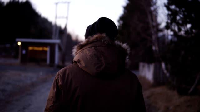 Aufnahmen vom Rücken eines Mannes, der am kalten Herbstnachmittag die Landstraße entlangläuft. Tragen Sie schwarzen Hut und Wintermantel mit der natürlichen Pelzhaube. Abenddämmerung. Kleine Hütte im Hintergrund – Video