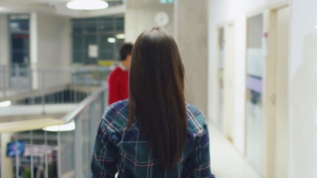 大学ロビーを歩いて魅力的な学生少女の後ろからの映像。 - 高等学校点の映像素材/bロール