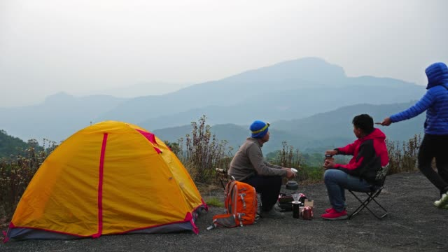 4K footage Group of asian people sitting and drinking beside tent comping in the deep forest over the scene of mountain landscape at the sunrise time, Traveler and camping concept video