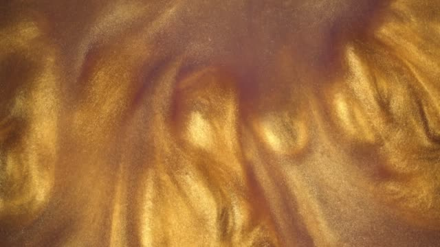 4K footage. Ink in water. Gold ink reacting in water creating abstract background.