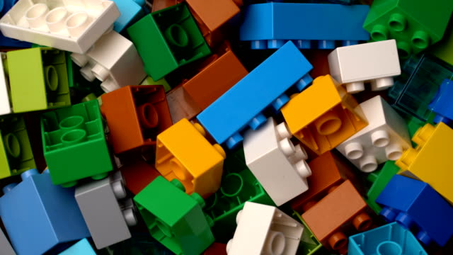 footage motion colorful plastic constructor rotate background texture - giocattolo video stock e b–roll