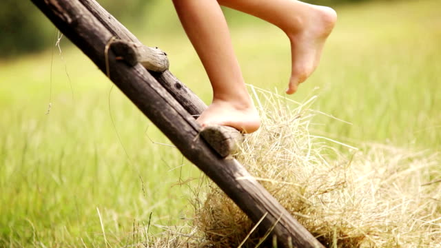 Footage of a barefoot boy climbing up the rural hut in the countryside video