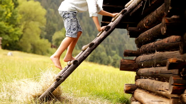 footage of a barefoot boy climbing up the rural hut in the countryside - ranch video stock e b–roll