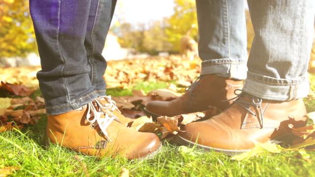 en film av ett par stövlar medan en kvinna kysser sin pojkvän - på tå bildbanksvideor och videomaterial från bakom kulisserna