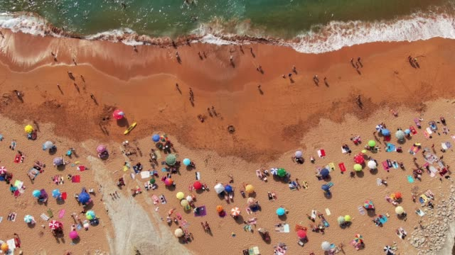 4K footage of a crowded beach in summer 4K resolution footage of a beautiful beach in Spain, crowded with tourists and beach umbrellas lounge chair stock videos & royalty-free footage