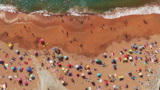 4k-aufnahmen von einem überfüllten strand im sommer - sun chair stock-videos und b-roll-filmmaterial