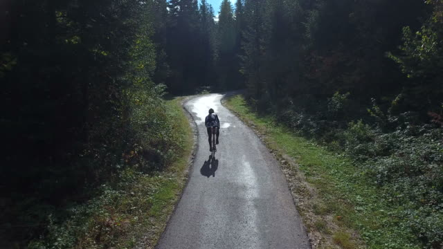 Footage of a cyclist training, he is cycling up a road in the woods video