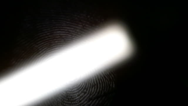 Footage of a fingerprint on a black surface being scanned