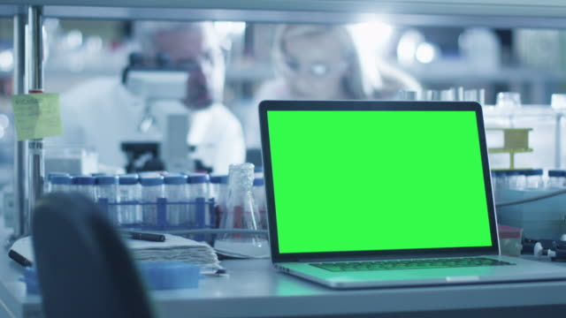 Footage of a laptop computer with green screen on a table in a laboratory. – Video
