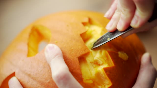 footage of a person carving out the teeth of a halloween pumpkin - zucca video stock e b–roll