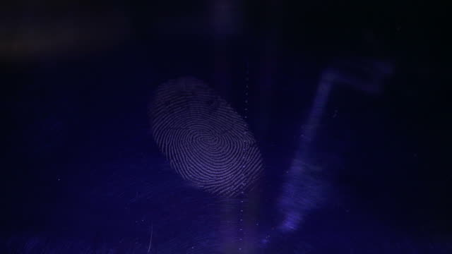 Footage of a person pressing his finger on a dark blue flat surface and leaves his fingerprint
