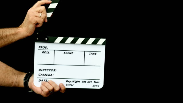 Footage of a person using a clapper board isolated on a black background Footage of a person using a clapper board isolated on a black background chair stock videos & royalty-free footage
