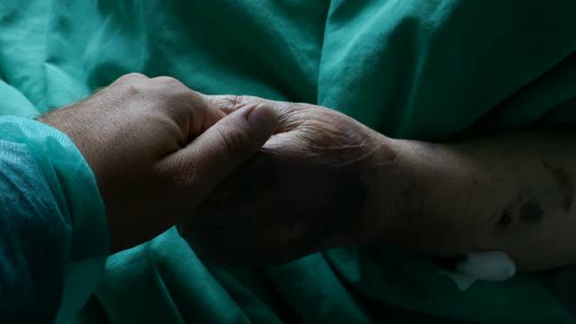 病院で祖母を訪問し、彼女の手をなでる人の映像 - 回復点の映像素材/bロール