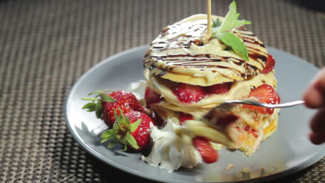 vídeos de stock e filmes b-roll de footage of a portion of pancakes decorated with strawberries on a plate lying on a table and a person takes a peace of it with a fork - molho arranjo