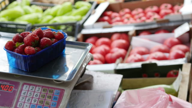 Footage of a seller at a fruits and vegetables market scales and packs some fresh strawberries for a customer
