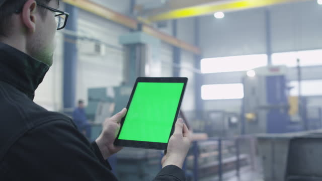 Footage of a tablet with green mock-up screen being used by a worker in industrial environment in a factory. video