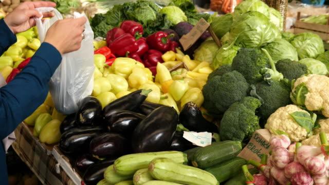 bilder av en kvinna på en marknad plocka några äggplantor och sätter dem i en plastpåse - pea sprouts bildbanksvideor och videomaterial från bakom kulisserna