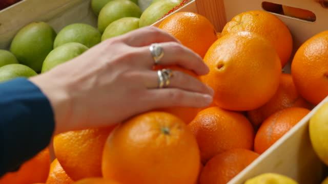 aufnahmen einer frau, die schöne orangen aus einer kiste pflücket - orange stock-videos und b-roll-filmmaterial