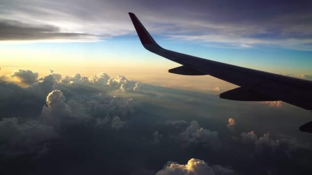 4k footage of airplane flying over the fantastic cloud and sky at the sunset time, travel and transportation concept - skrzydło samolotu filmów i materiałów b-roll