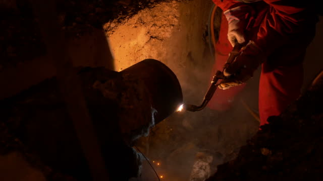 Footage of an intervention at night on a ruptured pipe, a worker is fixing the issue video
