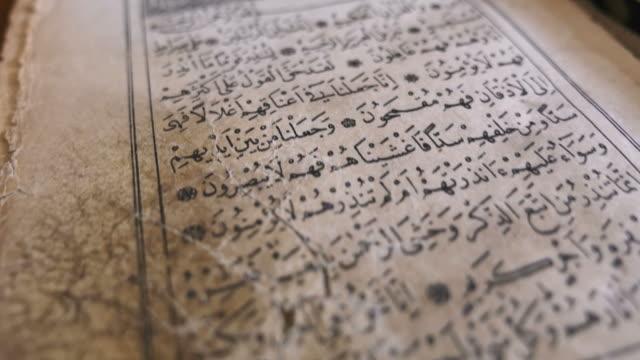 stockvideo's en b-roll-footage met beelden van een oude koran, het schot is beweging van beneden naar boven - koran