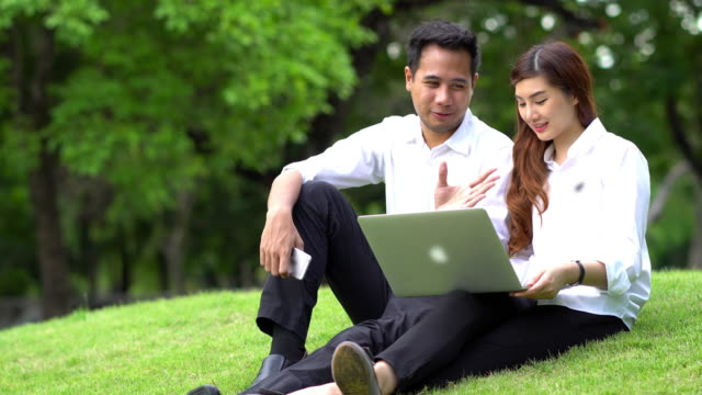 4K Footage of asian Businessman and Businesswoman with casual suit working with technology laptop at the outdoor park video