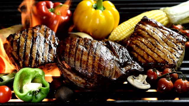 Footage of assorted grilled meat with vegetable on the flaming grill video