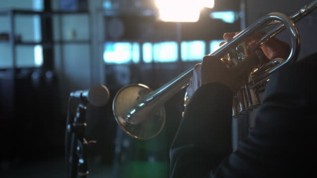 4K Footage of back side musician playing button and pushing on trumpet with microphone over the spot light in Music room background.planing from left to right video