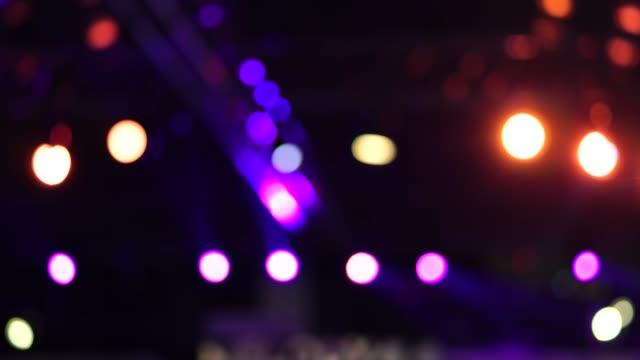 vidéos et rushes de séquences de 4k de concert volc et spotlight scène floue, déplaçant sur le fond sombre, le divertissement et le concept musical - lieu sportif