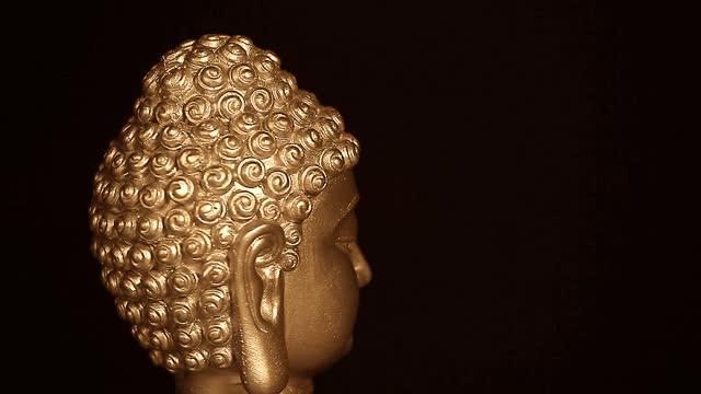 footage of buddha head dark background