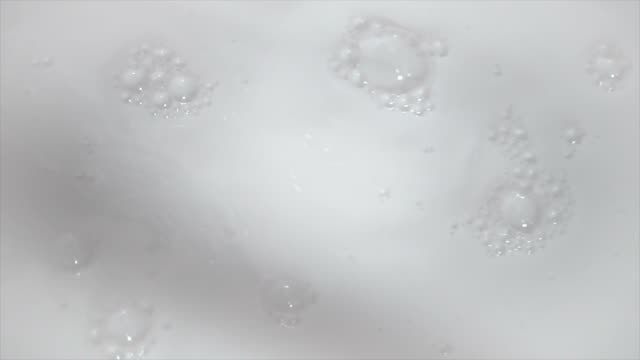 Footage of creamy milk smoothly moving with bubbles background for food dairy product