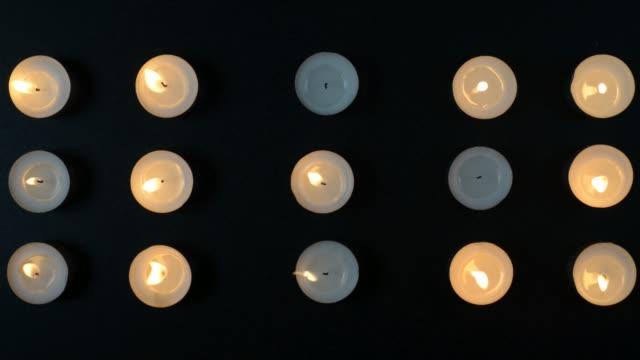 bilder av femton ljus brinnande och blekning av vinden på en svart bakgrund. - släcka bildbanksvideor och videomaterial från bakom kulisserna