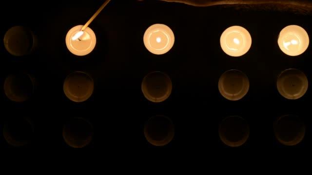 bilder av femton ljus inflammation med en match på en svart bakgrund. - släcka bildbanksvideor och videomaterial från bakom kulisserna