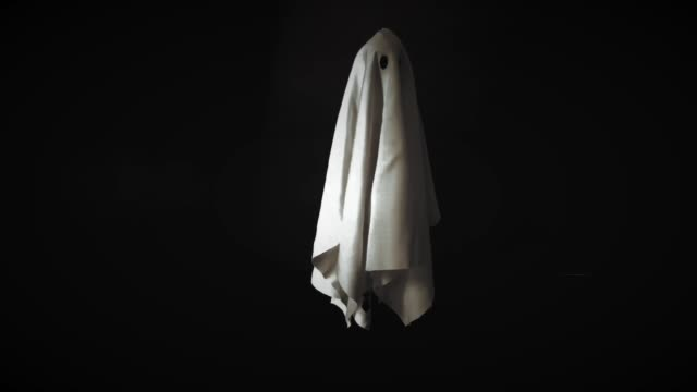Footage of ghost white sheet costume flying in the air with black background. Footage of ghost white sheet costume flying in the air with black background. Minimal Halloween scary concept. ghost icon stock videos & royalty-free footage
