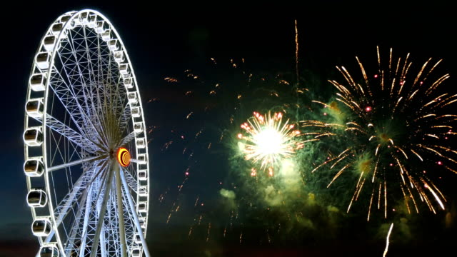 4k aufnahmen von riesenrad mit bunten feuerwerk-festival am himmel für die feier am abend hintergrund - volksfest stock-videos und b-roll-filmmaterial