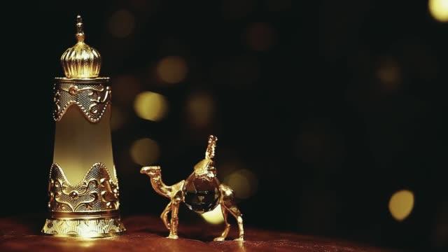 footage of glass perfume bottle camel dark background