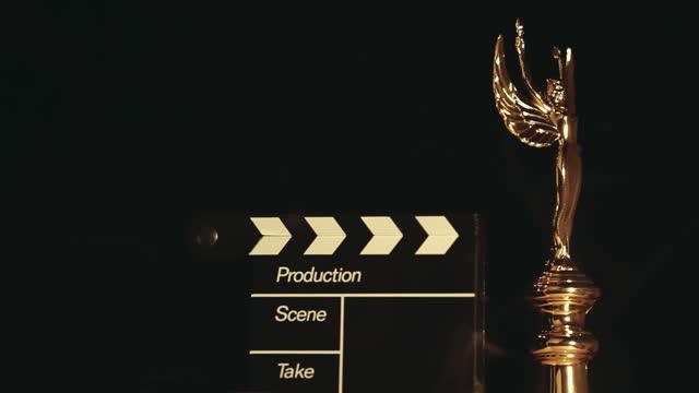 footage of gold statue clapper board smoke dark background