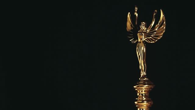 footage of gold statue dark background