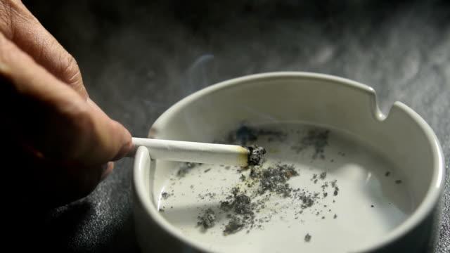 aydınlatılmış el koyarak ve bir kül tablası üzerinde sigara i̇çilmeyen görüntüleri - tütün mamulleri stok videoları ve detay görüntü çekimi