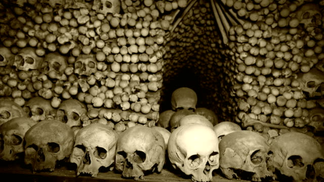 4K footage of Human's bones and skulls in the underground catacombs with old chronicle film effect after processing.