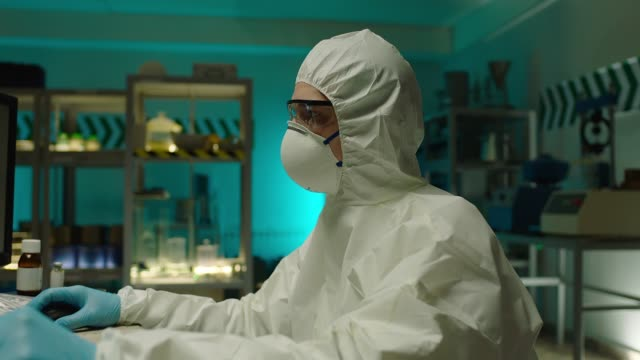 bilder av moderna laboratorium . i secure high level laboratory scientist i en coverall genomföra en forskning. forskare forska ny typ av corona virus nära datorn . - corona test bildbanksvideor och videomaterial från bakom kulisserna