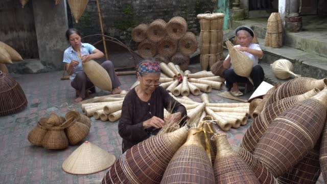 4K footage of Old Vietnamese female craftsman making the traditional bamboo fish trap or weave at the old traditional house in Thu sy trade village