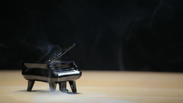 footage of piano smoke dark background