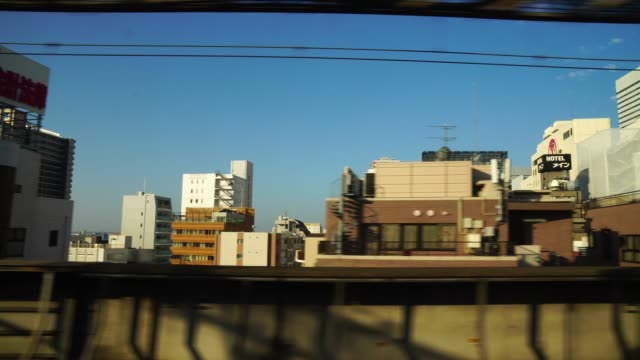 4k footage of scene from window of the japanese train (shinkansen) which running in tokyo cityscape and pass in the train station with silhouette, transportation concept - wagon kolejowy filmów i materiałów b-roll