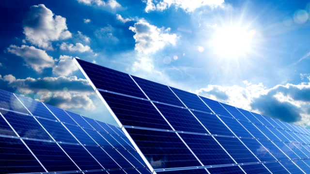 Footage of solar panels with the sun and the blue sky