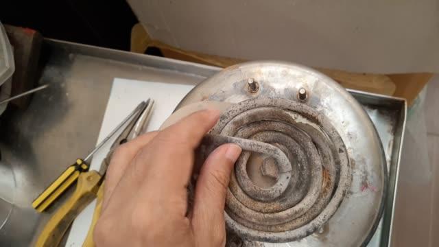 Footage of Technician Checking Broken Heater of Steam Iron