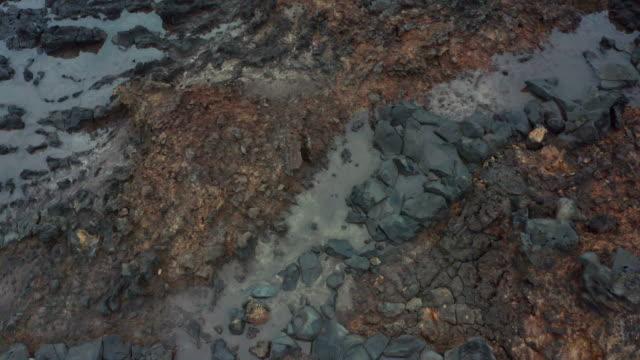 dokulu volkanik koyu renklerin 4k görüntüleri taşlar zemin yüzey drone görünümü... - kayaç stok videoları ve detay görüntü çekimi