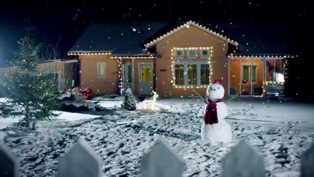 filmati dell'idilliaca casa decorata con ghirlande alla vigilia di natale, pupazzo di neve e albero di natale si trovano nel cortile di casa. bella serata invernale con neve soffice che cade. - decorare video stock e b–roll