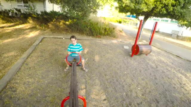pov-aufnahmen von drei kinder auf einem spielplatz spielen - kind schaukel stock-videos und b-roll-filmmaterial